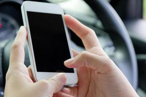 kvinna som håller den mobila enheten i bilen foto