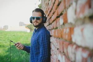 ung hipster man lyssnar på musik på en telefon