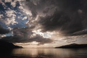molnen vid solnedgången över sjön foto