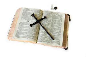 gammal bibel med korsläggning ovanpå, smörjande olja foto