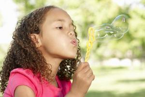 ung afrikansk amerikanflicka som blåser bubblor utanför