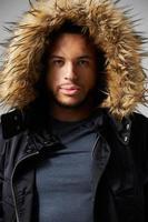 studio porträtt av ung man som bär vinterrock