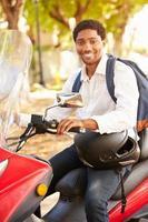 ung man som kör motorcykel till jobbet foto