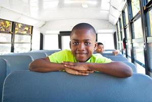 ung pojke på en skolbuss foto