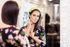 flicka som tittar i spegeln och försöker på blommig klänning
