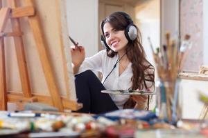 flicka i hörlurar målar med oljefärger på duk foto