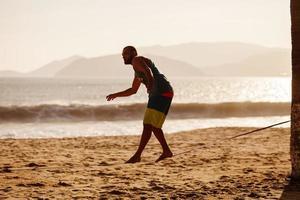 tonårig balansering på slackline med havsutsikt foto