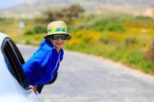 liten pojke reser med bil i sommarbergen