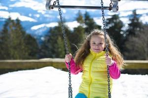 glad liten flicka som har kul på en gunga utomhus foto