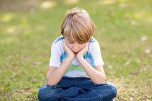 liten pojke som känner sig ledsen i parken