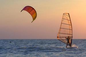 kitesurfing och vindsurfing vid solnedgången