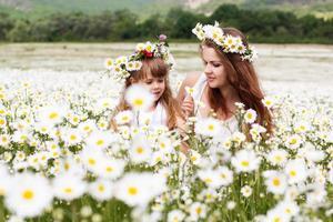 mamma med sitt barn som leker i kamomillfält foto