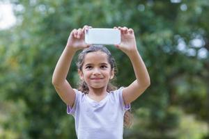liten flicka som använder sin telefon
