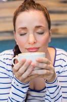 ung kvinna som har en cappuccino foto