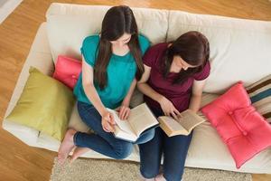 två vänner som läser böcker i soffan foto