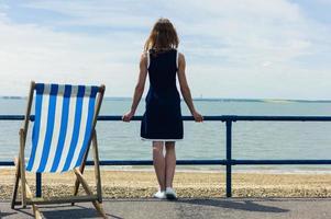kvinna som beundrar havet från strandpromenaden med en solstol foto