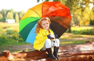 höststående liten flicka med färgglatt paraply utomhus i s