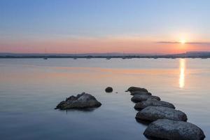 solnedgånghimmel över några stenar i stilla hamnvatten