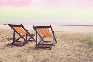 två spjälsäng på stranden, havet och himlen foto