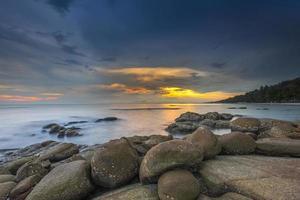hav med en solnedgång och molnig himmel