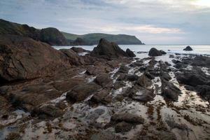 hopp cove solnedgång landskap marinmålning med stenig kust