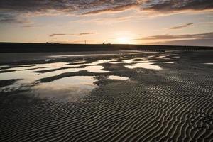 levande soluppgångslandskap reflekterat i lågvatten på stranden