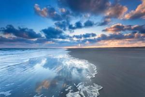 molnlandskap reflekteras i havet vid soluppgången foto