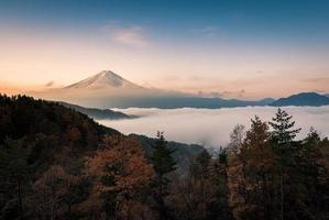 Mount Fuji inhölgat i moln med klar himmel foto