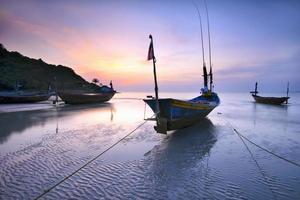 båtar på stranden under solnedgång ljus marinmålning i Thailand. foto