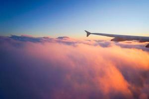 flygplanvinge i flyg från fönster, solnedgånghimmel