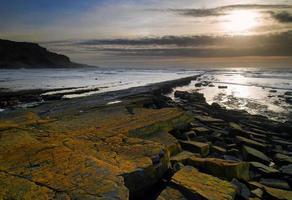 vackert marinmålningslandskap av stenig strand vid solnedgången foto