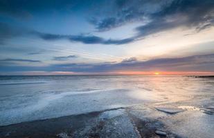 solnedgång vid frysta havet