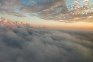 moln vid solnedgången från flygplanets fönster foto