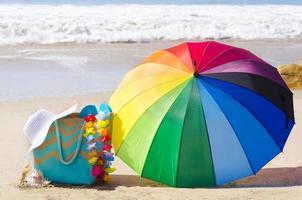 sommarbakgrund med regnbågsparaply och strandväska foto