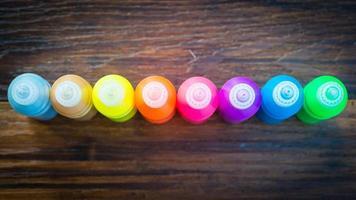 färgglad färg - flaskor med färgglada pigment på träbakgrund foto