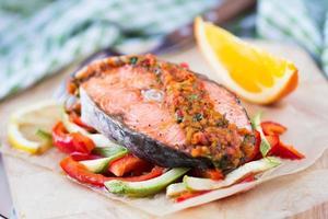 biff röd fisk lax på grönsaker, zucchini och paprika foto