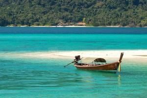 longtail båt i kristallklart turkosvatten och tropisk strand foto