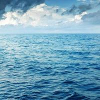 molnig blå himmel ovanför en blå yta av havet