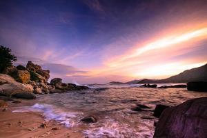 vågor som kraschar på stenig strand i solnedgången