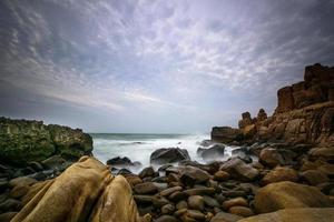 vågor som kraschar på stenig strand i gryningen