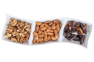 valnötter mandlar och dadlar i en vit skål