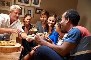 grupp vuxna vänner som äter pizza på ett husfest foto