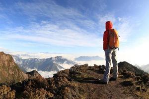 ung kvinna vandrare på vackra rullande moln bergstopp foto