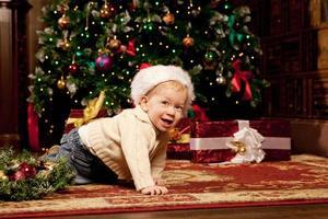 baby nära julgranen. liten pojke firar jul. foto