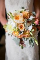 bröllopsbukett med rosor, georginer, lisianthus och dammiga millerblommor