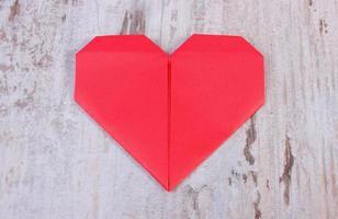 rött hjärta på gammalt trävitt bord, symbol för kärlek foto