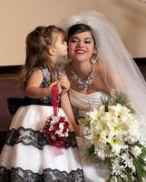 lilla syster kysser bruden på kinden. foto