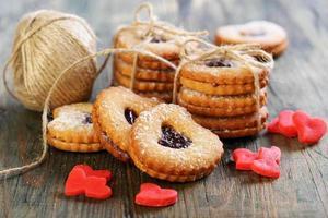 röda marsipanhjärtor, kakor och garnboll. foto