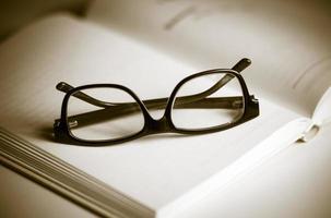 öppen bok och glasögon foto