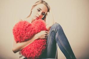 ledsen olycklig kvinna som håller den röda hjärtakudden foto